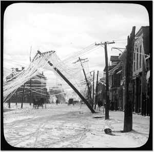 A street in Elora, Ontario after an ice storm - frozen utility lines are pulled over by weight of ice. (Photo captured between 1900 and 1919.)