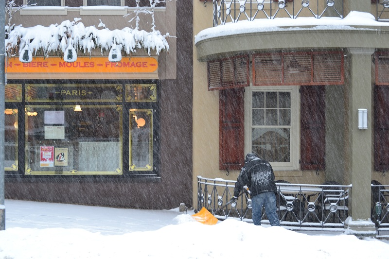A well-bundled gentleman shovels snow from a sidewalk in front of the Chestnut Hill Hotel.