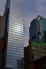 The sun reflects off the glass surface of a high rise in the West 50's.